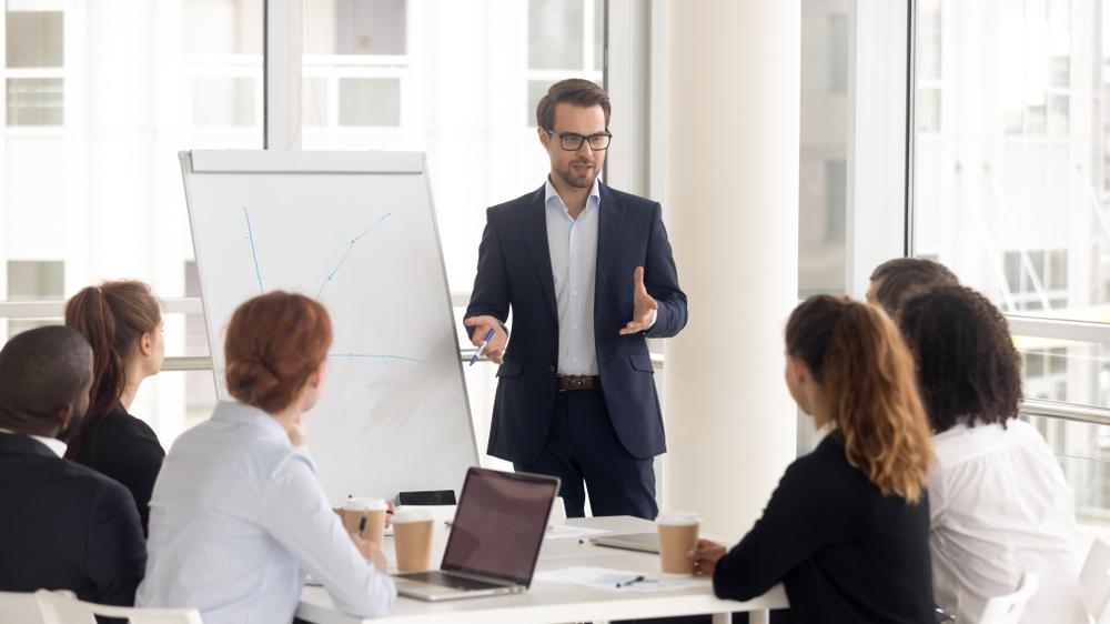 Male,Business,Coach,Speaker,In,Suit,Give,Flipchart,Presentation,,Speaker