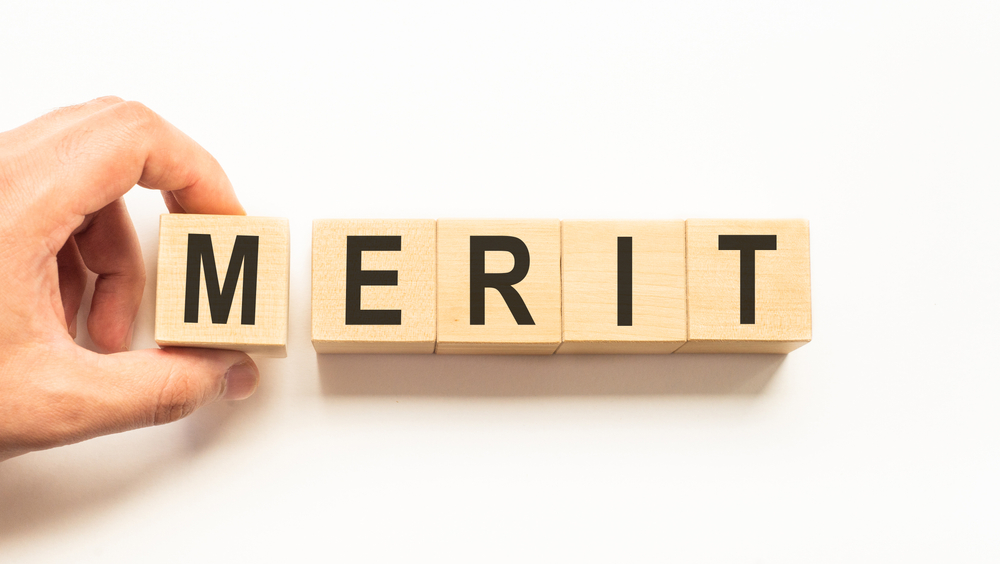 Word,Merit.,Wooden,Small,Cubes,With,Letters,Isolated,On,White