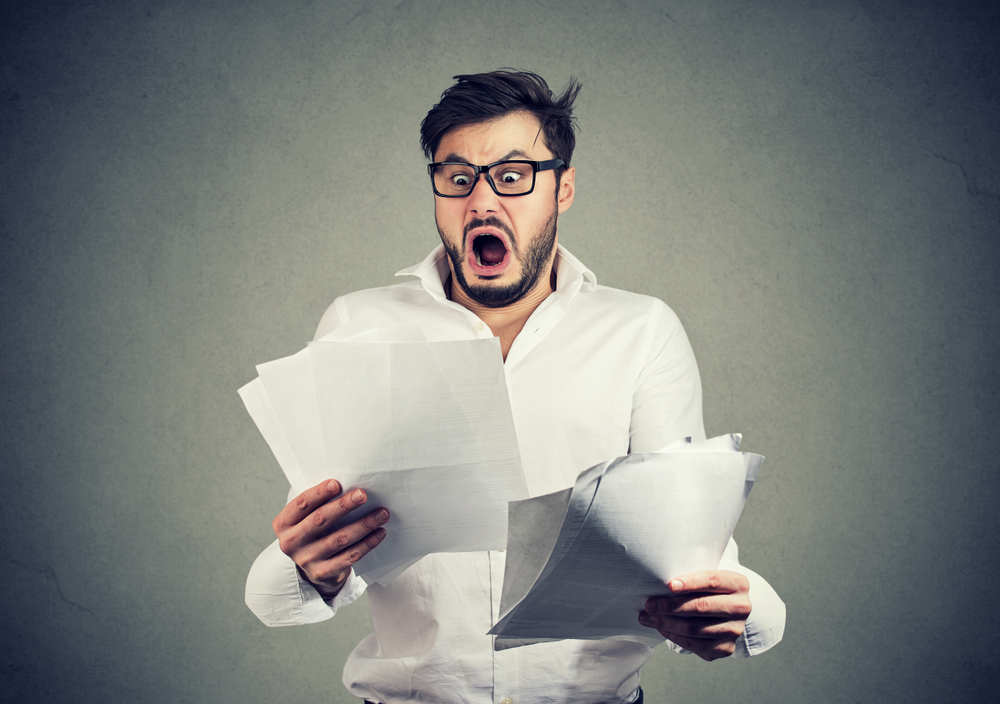 Young,Shocked,Guy,In,Glasses,Looking,At,Papers,Bank,Documents