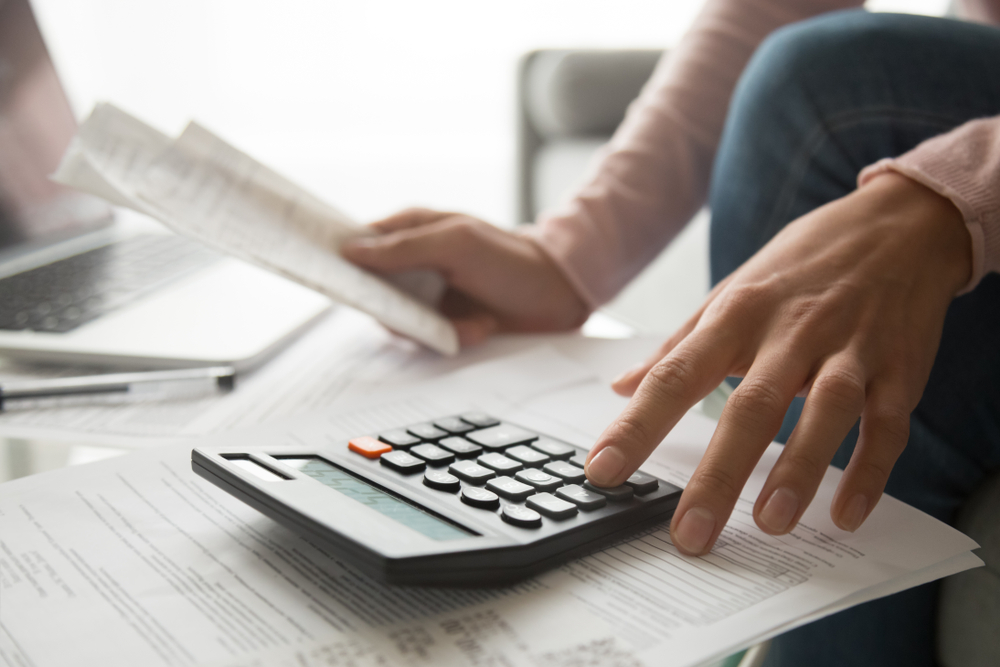 Woman,Using,Calculator,Holding,Paper,Bills,Calculating,Planning,Expenses,Money