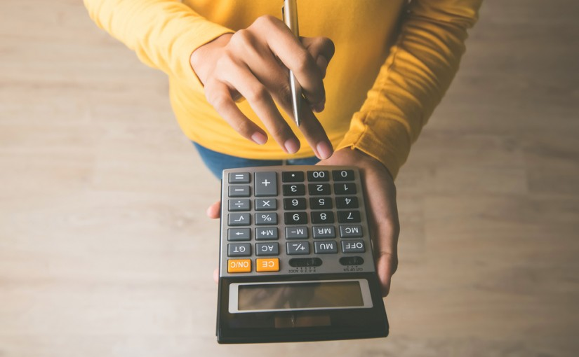 Woman,Entrepreneur,Using,A,Calculator,With,A,Pen,In,Her
